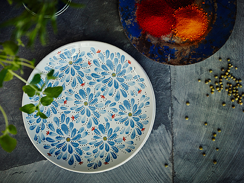 An off-white side plate in stoneware with blue floral pattern seen from above.