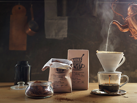 A display of packages filled with dark roasted filter coffee and a coffee cup made of glass with freshly brewed coffee.