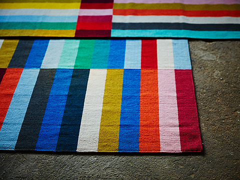 A colourful striped rug in twelve different colours.
