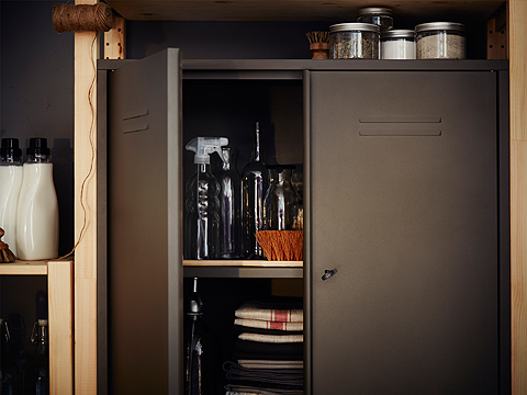 Close-up of a grey steel cabinet with one door open. Inside the cabinet you can see glass bottles, a spray bottle and tea towels.