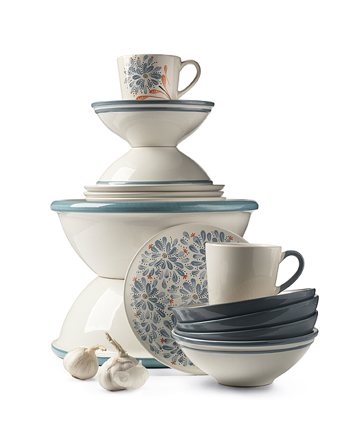 A display of mugs, bowls, plates and serving bowls in off-white stoneware with floral patterns or blue edges.