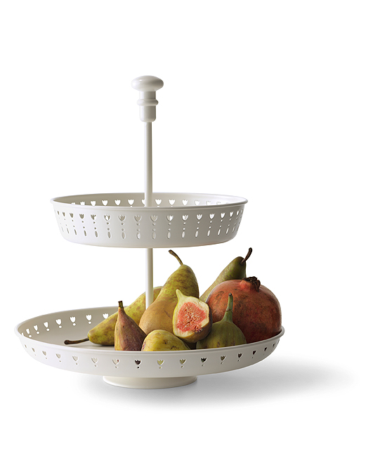 A white serving stand with two tiers, shown with pears, figs and pomegranates.