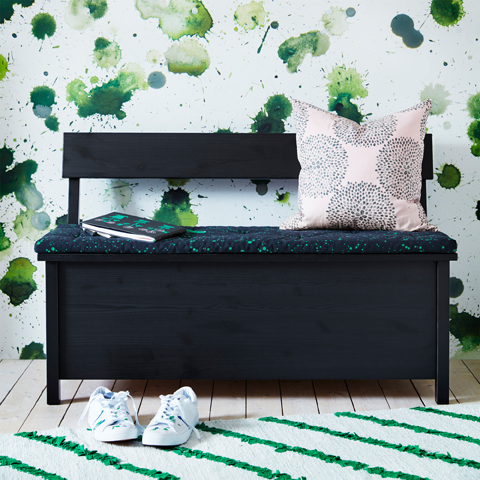 A black storage bench with seat pad in black with green floral pattern.