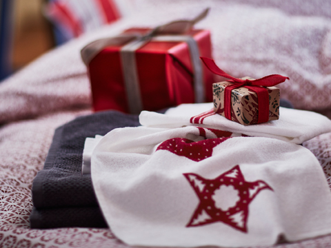 Close-up of a white guest towel with red stars and wrapped Christmas presents.