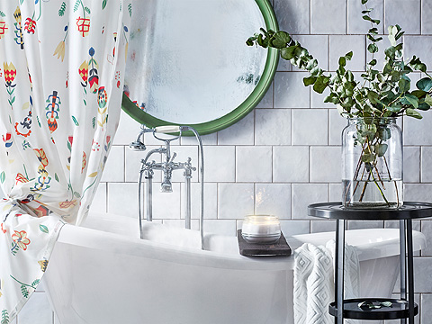 A round green mirror hanging above a bathtub. Shown together with a colourful shower curtain and a lit scented candle.