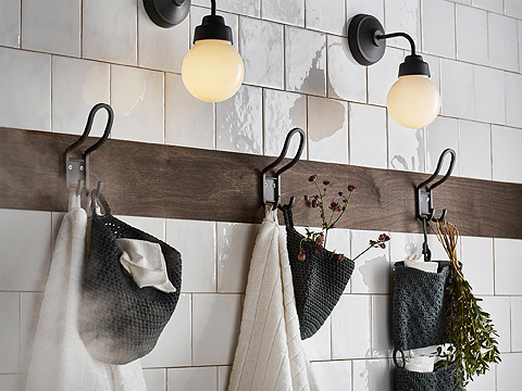 A white tile wall with a brown board and three black hooks with towels.