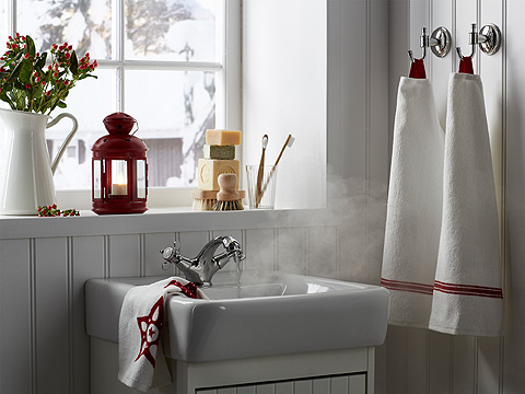 Two white towels hanging on the wall, beside a white bathroom sink. Shown together with a red lantern in the window.