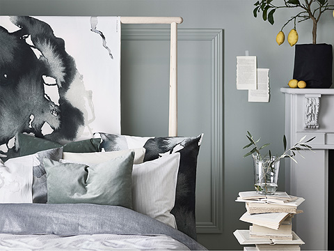 A high poster bed with bedlinen in white, grey and black.