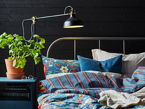 A black metal bed with bedlinen in blue, red, yellow and white. Shown together with a black floor lamp.