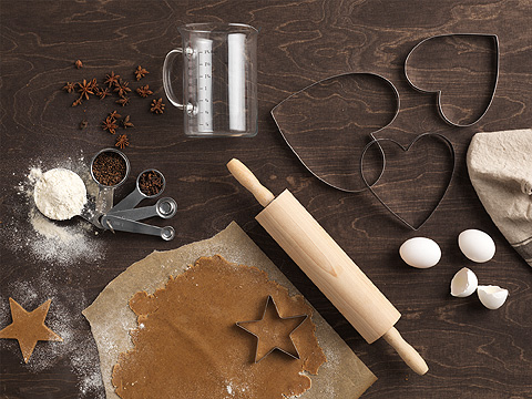 Heart-shaped pastry cutters, rolling pin and measuring cups, seen from above.