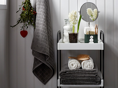 A bathroom trolley filled with grey and white towels, a glass jar with cotton and a mirror.
