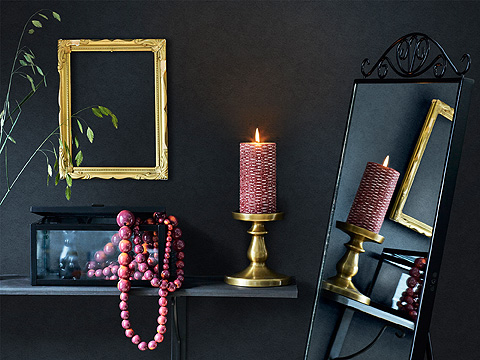 A black standing mirror shown together with a brass-colored block candle holder with a lit candle and a gold-colored picture frame.