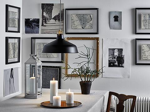 A wall filled with picture frames in black and gold-color with black/white pictures. A beige tablecloth on a table with a silver-colored lantern and three lit candles on a candle dish.