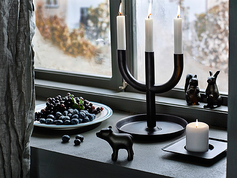 A black three-armed candlestick with lit candles, shown together with a candle dish with a lit block candle.