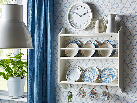 A white plate shelf filled with plates in different sizes and with different patterns. With hooks underneath for mugs.