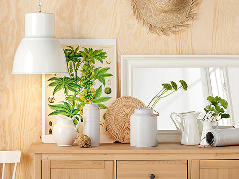 A sideboard in solid pine with a milk jug, plant pots and a mirror displayed on the top, all in white.