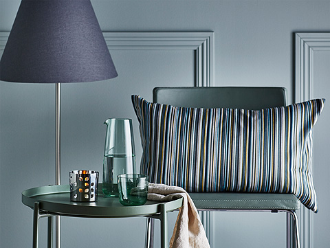 A striped cushion on a leather chair, shown together with a tray table and a glass carafe, all in green-turquoise colours.