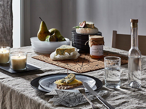 A set table with patterned glass plates and glasses, shown together with different cheeses and pears.
