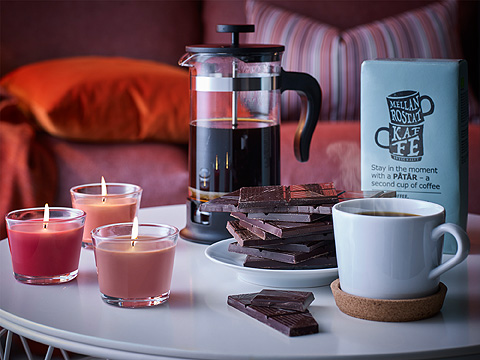 A side table set with a coffee/tea maker filled with coffee, a plate with dark chocolate and a white coffee cup on a cork coaster.