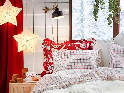 A bed with bedlinen in red and white, shown together with two lamp shades shaped as stars.