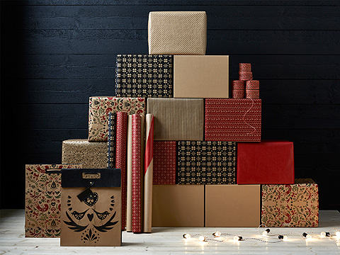 A lighting chain in front of a pile of boxes wrapped in gift wrap in different patterns.
