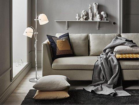 A floor lamp with two shades that you can adjust in height and aim the light where you need it. Shown together with a beige sofa and cushions.