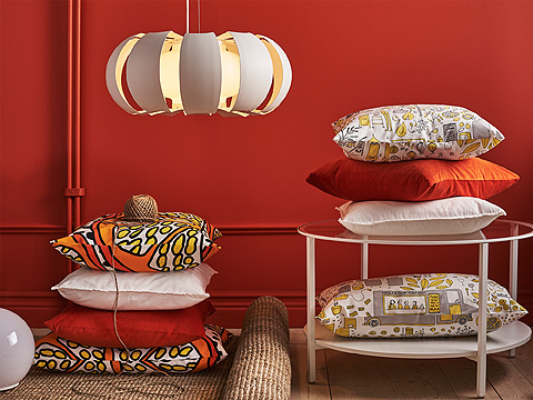 Piles of cushions in white, red and orange shown together with a white pendant lamp.