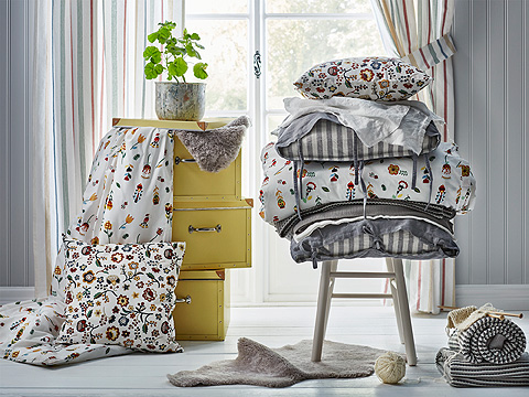 A display of yellow boxes and bedlinen with stripes and floral pattern.