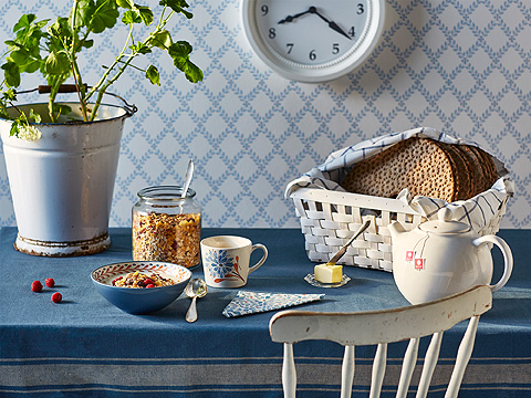 A breakfast table with a blue bowl filled with cereals, a mug with tea and a basket with crispbread.