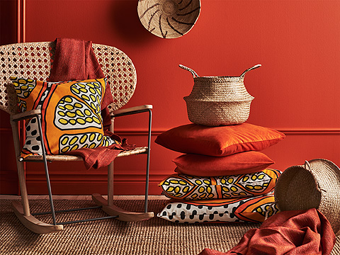 A pile of orange cushions in different sizes and with different patterns. Shown together with a rocking-chair made of rattan and solid ash.