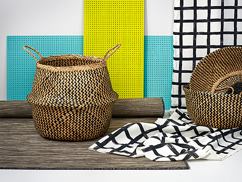 A handwoven basket in seagrass shown together with a grey/black rug and a metre fabric with black/white square pattern.
