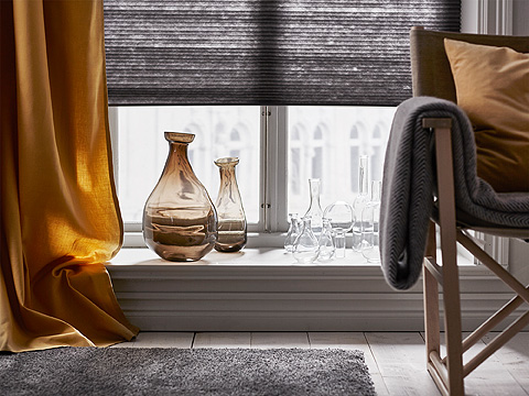 A windowsill with two large brown glass vases and several small clear glass vases.