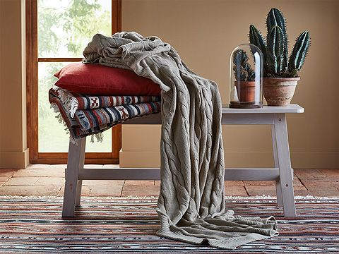 A grey bench with a beige throw, an orange cushion and a colorful rug.