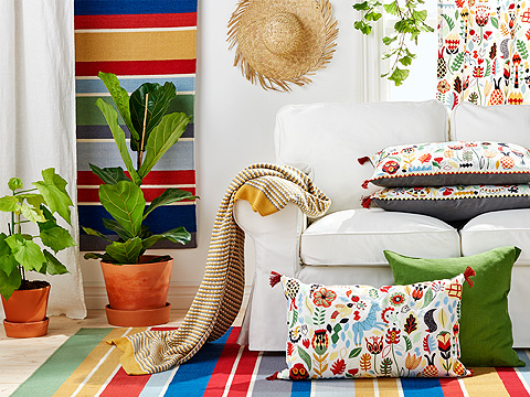 Colourful, embroidered cushions and rugs, shown together with a white sofa.
