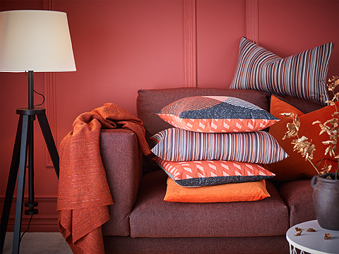 A pile of orange cushions in different sizes and with different patterns, shown in a wine-red sofa.