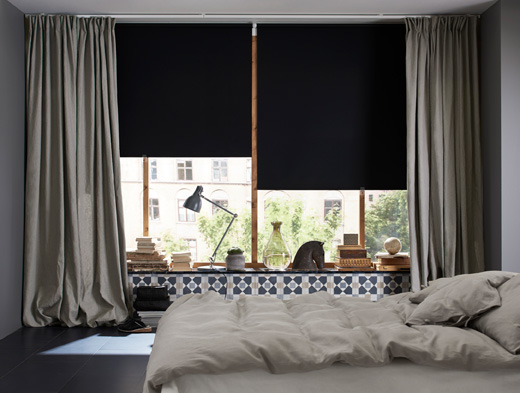 A bedroom featuring large windows with black black-out roller blinds and one layer of thick grey curtains for cozyness and silence.