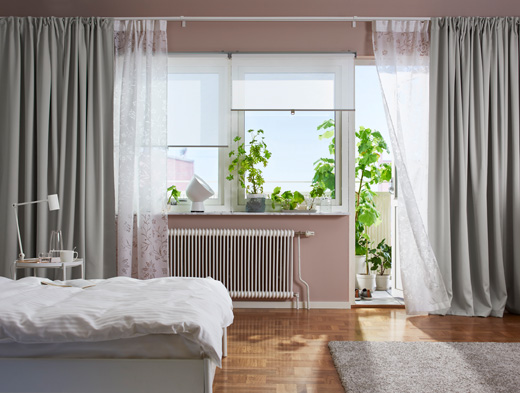 A bright bedroom featuring windows with white roller blinds, one layer of sheer white curtains that filters the daylight and one layer of grey thick block-out curtains for privacy.