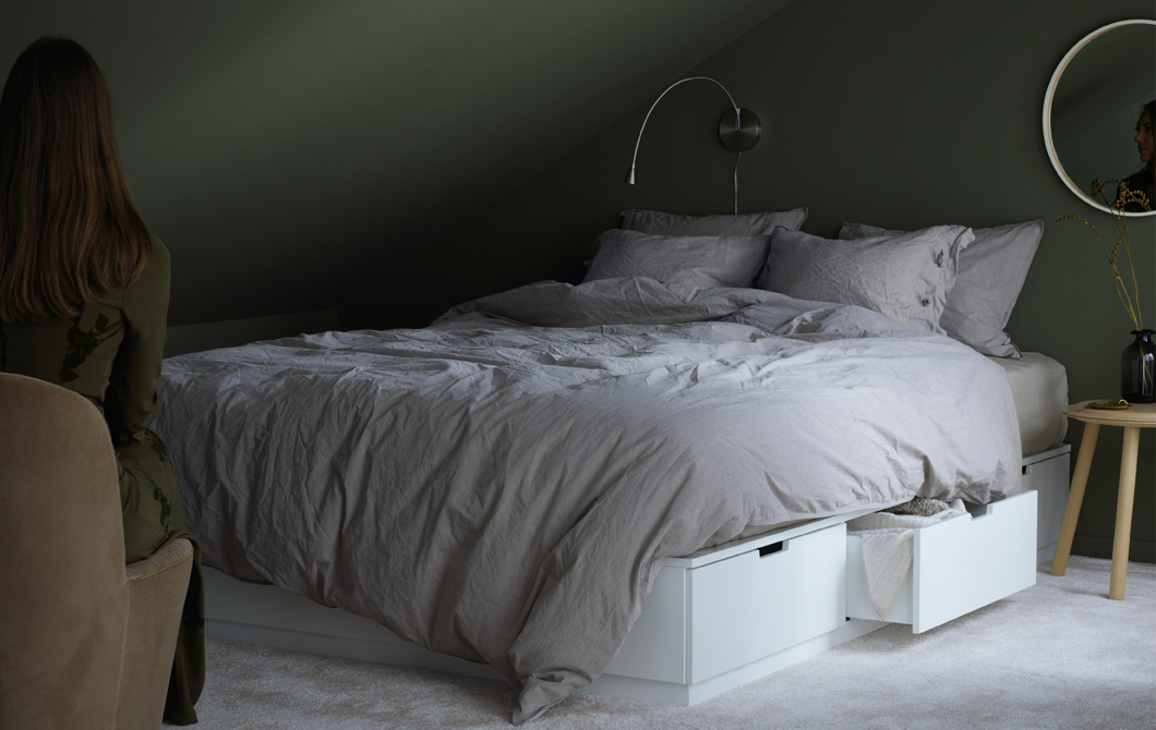A bedroom with a white bed that includes six soft-closing drawers for extra cushions and blankets, three on each side.