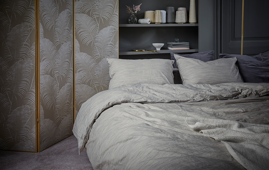 A bed with quilt cover and two pillowcases made of beige 100% cotton with fine shifting colors, shown in a grey bedroom.