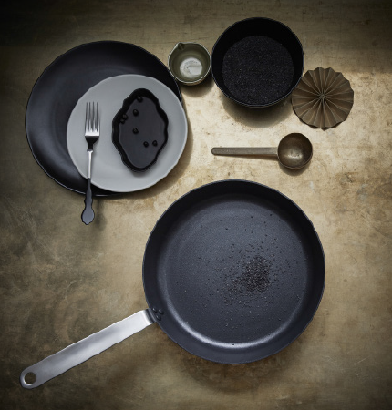 A stanless steel frying pan, seen from above, together with a black and a grey plate, and a small bowl with black peppercorns.