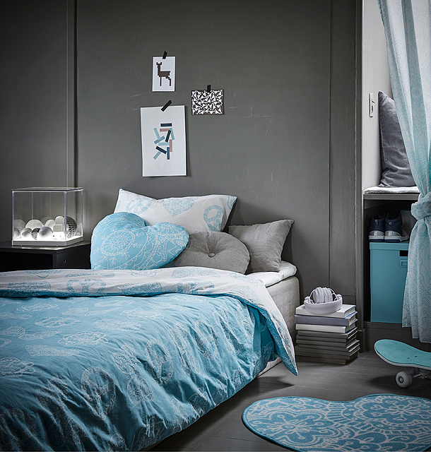 A children's room decorated with quilt cover, pillowcases, cushions and rugs in turquoise and white with mandala-inspired pattern.