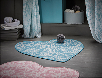 A turquoise heart-shaped rug with mandala-pattern.