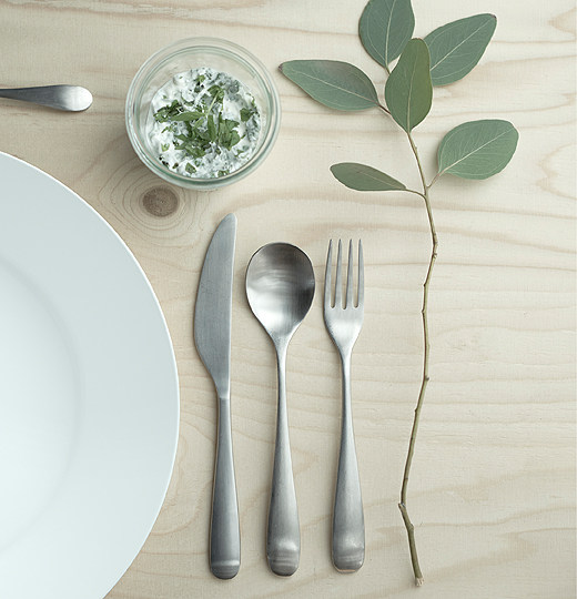 A table setting with stainless steel cutlery, a glass, a white stoneware plate and a green twig.