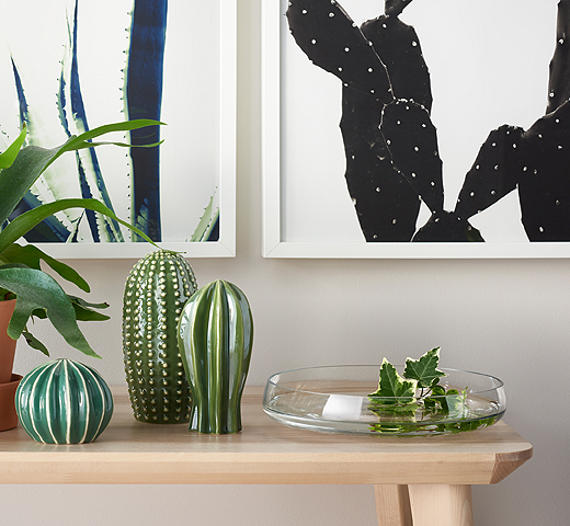 A set of three ceramic cactuses indifferent shapes and sizes, shown together with a low glass bowl decorated with ivy.