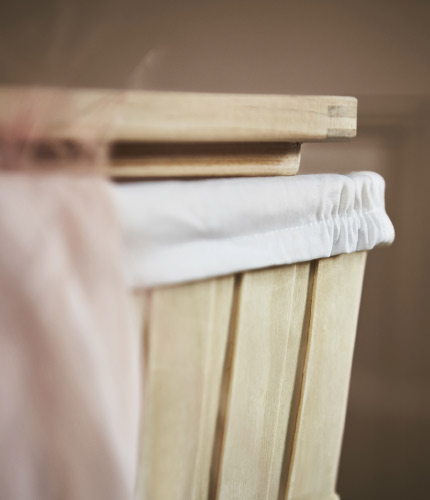 Close-up of a laundry basket made of solid wood, comes with a lid and an inner bag that is removable and washable.