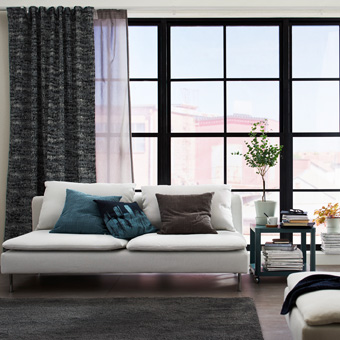 A living room featuring large mullion windows with one layer of white and grey sheer curtains that filters the daylight and one layer of black block-out curtains for privacy.