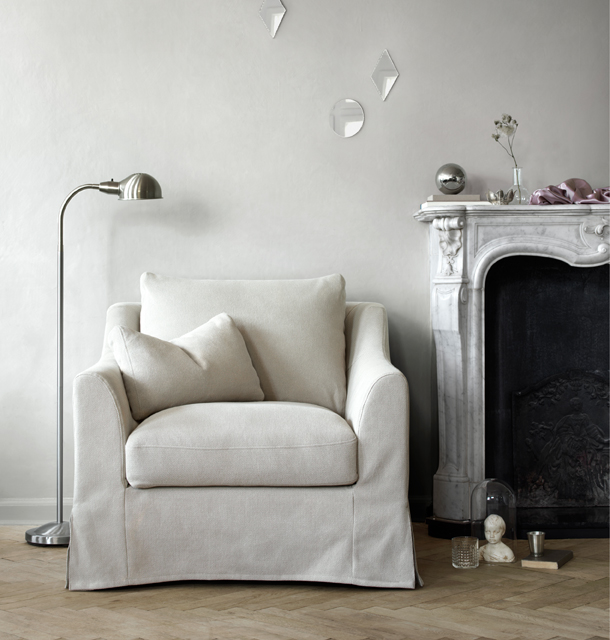 A light living room with a generous sized armchair that has an additional loose cushion, beige cover in a cotton/linen blend.