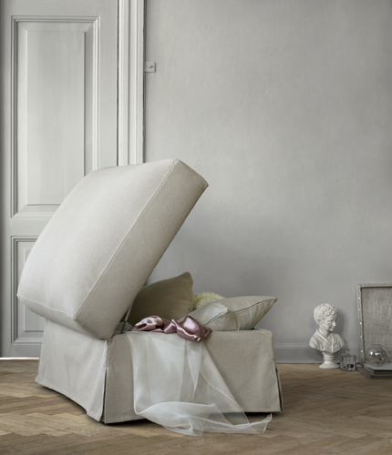 A light living room with a footstool, in a beige cover, that features hidden storage for extra cushions and blankets.