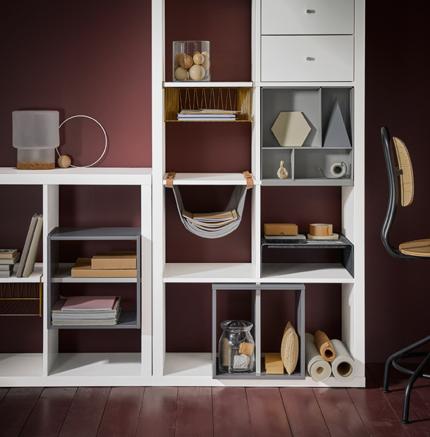 A white shelving unit filled with different inserts, such as brass-coloured wire baskets, hanging organiser with leather straps, light grey shelf dividers and storage with compartments.