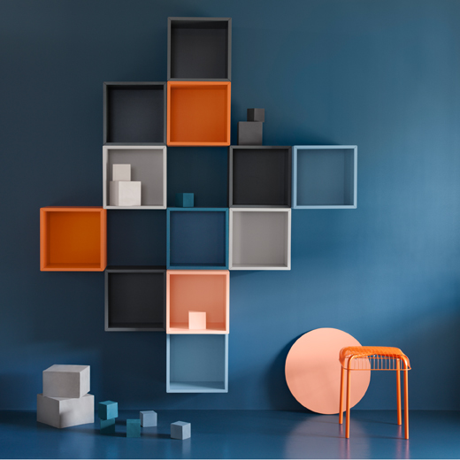 A blue wall with square-shaped cubes in grey, orange and blue.